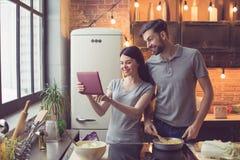 Jeunes couples faisant cuire dans la cuisine Images libres de droits