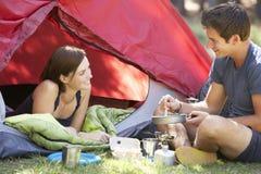 Jeunes couples faisant cuire le petit déjeuner des vacances de camping Photos libres de droits