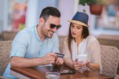 Jeunes couples faisant des achats en ligne par le téléphone et la carte de crédit futés au café, foyer sélectif photo stock