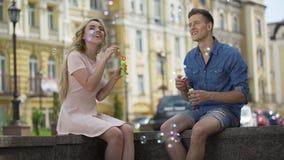 Jeunes couples faisant des bulles de savon, s'atteignant au baiser, enjouement banque de vidéos
