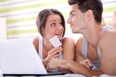 Jeunes couples faisant des emplettes au-dessus de l'Internet Photos stock
