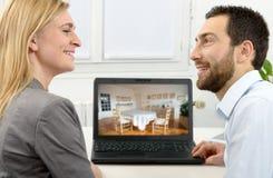 Jeunes couples faisant des emplettes en ligne à la maison Photos stock