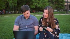 Jeunes couples faisant des emplettes en ligne utilisant l'ordinateur portable et la carte de crédit banque de vidéos