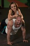 Jeunes couples faisant des pompes dans le gymnase Photos stock