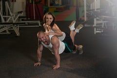 Jeunes couples faisant l'exercice de pompe dans le gymnase Photos libres de droits