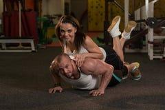 Jeunes couples faisant l'exercice de pompe dans le gymnase Photos stock