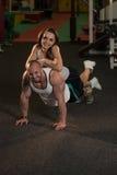 Jeunes couples faisant l'exercice de pompe dans le gymnase Images stock