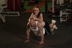 Jeunes couples faisant l'exercice de pompe dans le gymnase Photo stock