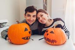 Jeunes couples faisant la cric-o-lanterne pour Halloween sur la cuisine L'homme et la femme heureux ont préparé des potirons pour photos libres de droits