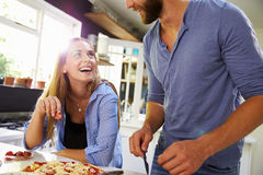 Jeunes couples faisant la pizza dans la cuisine ensemble Photographie stock libre de droits