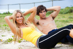 Jeunes couples faisant le Sit-Ups par l'océan Photo stock