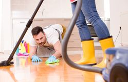 Jeunes couples faisant les travaux domestiques ensemble Image stock
