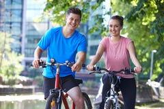 Jeunes couples faisant un cycle à côté de la rivière dans l'environnement urbain Photographie stock libre de droits