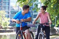 Jeunes couples faisant un cycle à côté de la rivière dans l'environnement urbain Photo stock