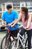 Jeunes couples faisant un cycle à côté de la rivière dans l'environnement urbain Photos libres de droits