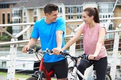 Jeunes couples faisant un cycle à côté de la rivière dans l'environnement urbain Images stock