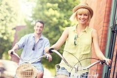 Jeunes couples faisant un cycle ensemble dans la ville Photo libre de droits