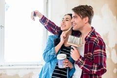 Jeunes couples faisant un selfie tout en travaillant à la rénovation de leur maison photo stock