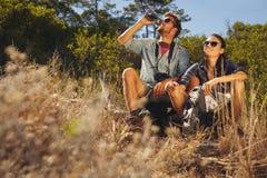 Jeunes couples faisant une pause sur la hausse Photo stock