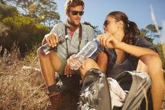 Jeunes couples faisant une pause sur une hausse photos stock