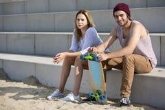 Jeunes couples faisants de la planche à roulettes sur une plage Photographie stock