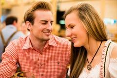 Jeunes couples flirtant dans la tente de bière d'Oktoberfest Images stock