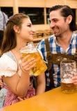 Jeunes couples flirtant dans la tente de bière d'Oktoberfest Image libre de droits