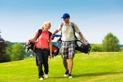 Jeunes couples folâtres jouant au golf sur un cours Photo stock
