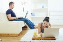 Jeunes couples fonctionnant à la maison Photos libres de droits