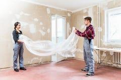 Jeunes couples fonctionnant ensemble à la rénovation de l'intérieur de leur maison images libres de droits