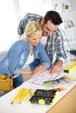 Jeunes couples fonctionnant ensemble pour la maison photos stock