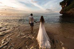 Jeunes couples fonctionnant le long de l'eau sur la plage photo libre de droits