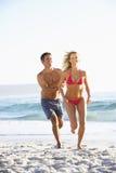 Jeunes couples fonctionnant le long de Sandy Beach en vacances Photos stock