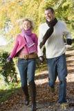 Jeunes couples fonctionnant le long du chemin de régfion boisée Image stock