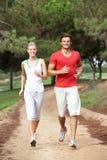 Jeunes couples fonctionnant par le stationnement Photo stock