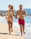 Jeunes couples fonctionnant près de la mer Images libres de droits