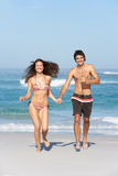 Jeunes couples fonctionnant sur les vêtements de bain s'usants de plage Photo stock