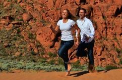 Jeunes couples fonctionnant sur une dune de sable Images stock