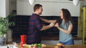 Jeunes couples fous dans l'amour dansant ensemble la danse de rocknroll dans la cuisine à la maison en vacances banque de vidéos