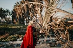 Jeunes couples frais jouant et luttant avec des branches de palmier dehors Photo stock
