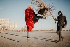 Jeunes couples frais jouant et luttant avec des branches de palmier dehors Photo libre de droits