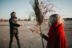 Jeunes couples frais jouant et luttant avec des branches de palmier dehors Photographie stock libre de droits