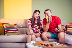 Jeunes couples géniaux mangeant de la pizza sur un divan Photo libre de droits