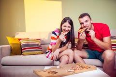 Jeunes couples géniaux mangeant de la pizza sur un divan Photos stock