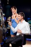 Jeunes couples gagnant à la machine à sous Photo libre de droits