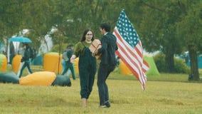 Jeunes couples gais au festival de parc sous la pluie se renversante avec le drapeau unated d'états banque de vidéos