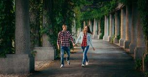Jeunes couples gais de marche par la main le long de l'arcade de Hall centennal à Wroclaw, Pologne envahie avec des usines Image libre de droits