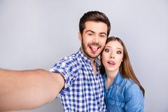 Jeunes couples gais géniaux faisant la photo de selfie sur l'appareil-photo du ` s de type Images stock