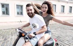 Jeunes couples gais montant un scooter et ayant l'amusement Images stock