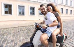 Jeunes couples gais montant un scooter et ayant l'amusement Photographie stock libre de droits